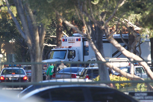 Las Vegas police investigate the scene of an officer-involved shooting that left a suicidal man with a rifle dead at an apartment complex on the 5300 block of East Craig Road off of Las Vegas Boul ...