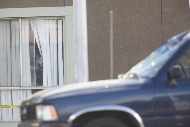 A woman looks out from her window as Las Vegas police investigate the scene where a pedestrian was struck by a vehicle on Eastern near Karen avenues, in Las Vegas on Monday, Feb. 16, 2015. The ped ...