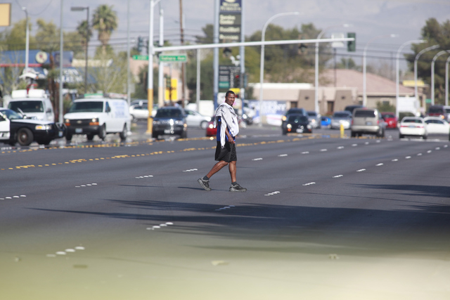 A man illegally crosses the road as Las Vegas police investigate the scene where a pedestrian was struck by a vehicle on Eastern near Karen avenues, in Las Vegas on Monday, Feb. 16, 2015. The pede ...
