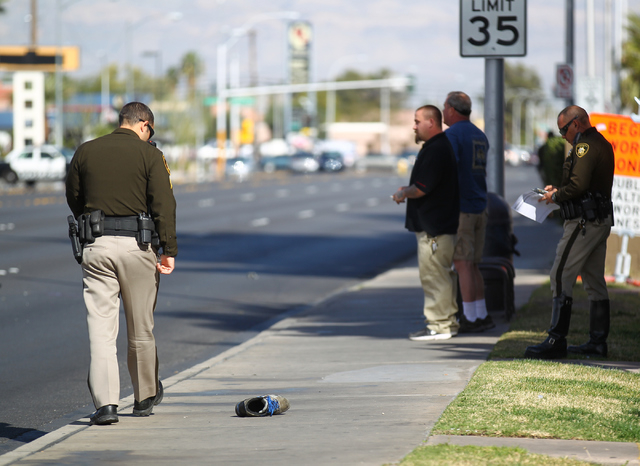 A Las Vegas police officer walks by a lone shoe as police investigate the scene where a pedestrian was struck by a vehicle on Eastern near Karen avenues, in Las Vegas on Monday, Feb. 16, 2015. The ...