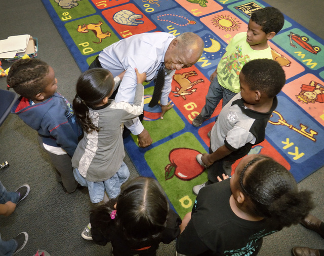Dr. Robert Green, who served as Dr. Martin Luther King Jr.'s director of education, gets some help up after sitting down and talking with students in teacher Ashley Wright's kindergarten class at  ...