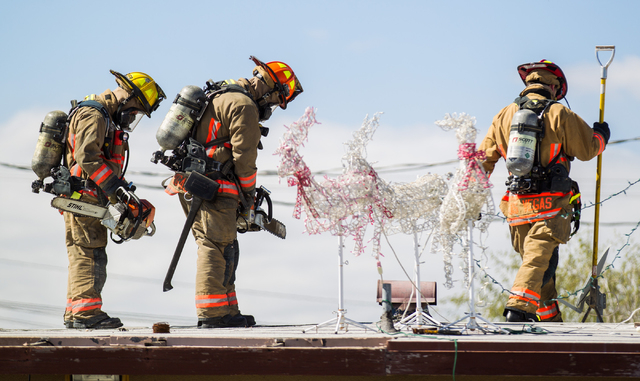 Las Vegas Fire & Rescue firefighters and officials respond to a house fire that left the home gutted, near Rancho and Vegas drives in Las Vegas on Friday, Feb. 27, 2015. One victim was transported ...