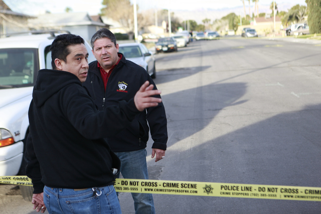 Las Vegas homicide Lt. Ray Steiber, right, speaks with an unidentified man inquiring about the situation, at the scene of a shooting where a man was fatally shot in his garage on the 6400 block of ...
