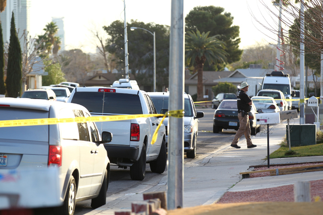 Las Vegas police investigate the scene where a man was fatally shot in his garage on the 6400 block of Gunderson Boulevard, near Torrey Pines Drive and Harmon Avenue, in Las Vegas on Monday, Feb.  ...