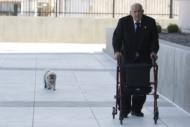 Salvatore Ruvolo, co-defendant in a federal case involving fraud and corruption at Las Vegas homeowners associations, walks to Lloyd George Federal Courthouse in Las Vegas with his dog Scooter Wed ...
