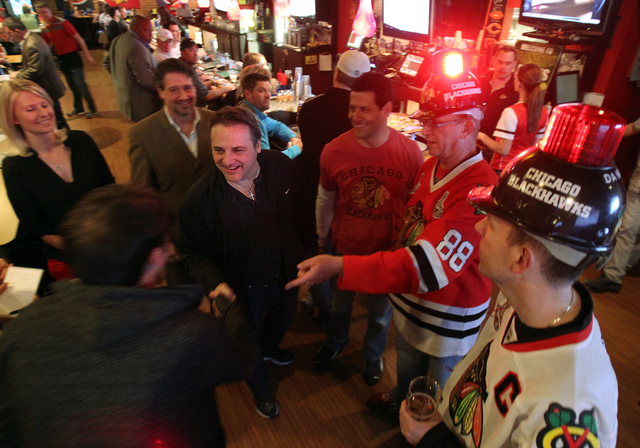 Gavin Maloof, center, shakes hands with Mike McHugh, left, at Brando's Sports Bar at 3725 Blue Diamond Road in Las Vegas during a watch party for the Chicago Blackhawks-Los Angeles Kings NHL hocke ...