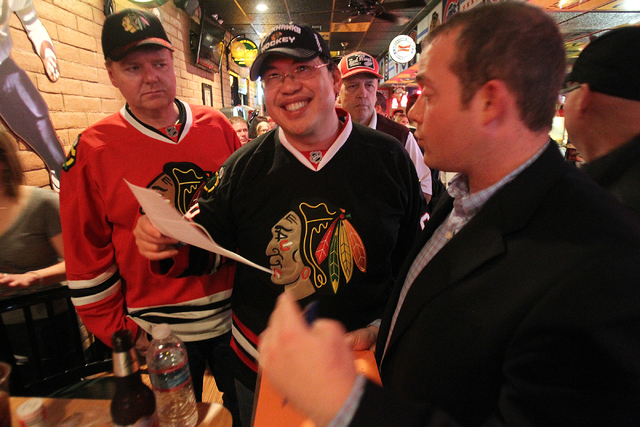 Marvin Tay, center, smiles after putting a deposit on season tickets for a future Las Vegas NHL team at Brando's Sports Bar at 3725 Blue Diamond Road in Las Vegas during a watch party for the Chic ...