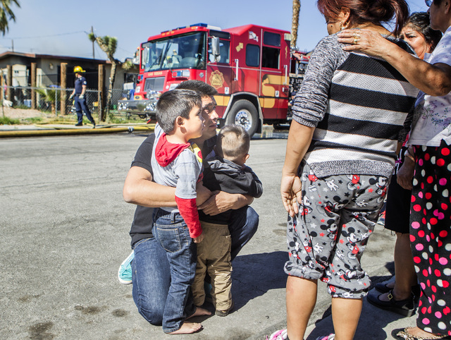 A man who declined give his name hugs his 4-year-old and his 2-year-old sons Friday, Feb. 27, 2015, after a fire broke out at the boys' home, located north on U.S. Highway 95 and east of Rancho Dr ...