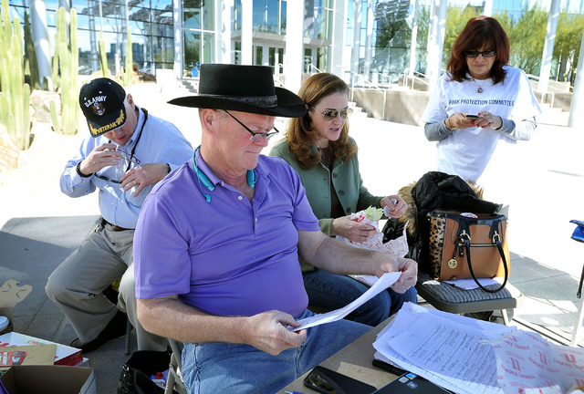 Las Vegas City Councilman Bob Beers, second left, reviews signatures as he is surrounded by supporters, from left, Bruce Feher, Suzette LaGrange and Lisa Mayo, of his initiative to put the Las Veg ...