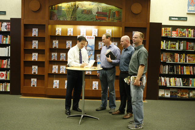 U.S. Sen. Marco Rubio, R-Fla., from left, signs a copy of a book for his childhood friends from left, Bryan Thiriot, and his brothers Bryce, and Nathan during a book signing of his book, American  ...