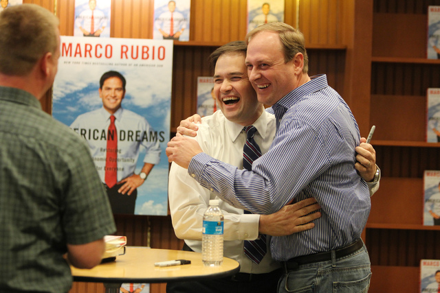 U.S. Sen. Marco Rubio, R-Fla., left, hugs his childhood friend Bryan Thiriot who was first in line during a book signing of his book, American Dreams: Restoring the Land of Opportunity, at Barnes  ...