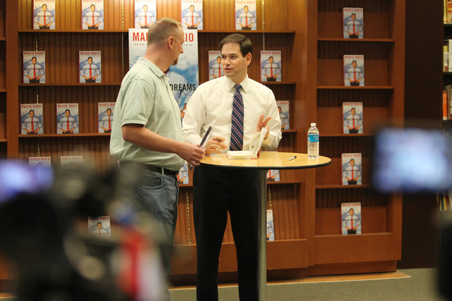 U.S. Sen. Marco Rubio, R-Fla., right, signs his book for Ryan Brooks, government teacher at Cimarron High School, during a book signing of his book, American Dreams: Restoring the Land of Opportun ...