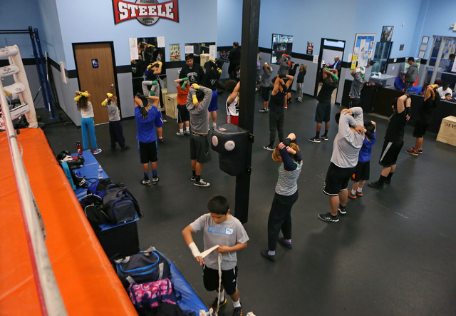 Children stretch and prepare to start a workout during a youth boxing fitness class for students ages 8 to 18 at the Richard Steele Boxing Club Wednesday, Jan. 21, 2015, in North Las Vegas. The cl ...