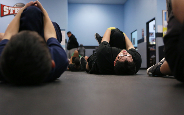 Raymond Corona, 17, right, stretches during a youth boxing fitness class for students ages 8 to 18 at the Richard Steele Boxing Club Wednesday, Jan. 21, 2015, in North Las Vegas. The club, which i ...