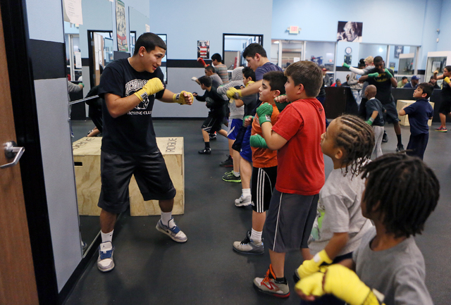 Jerardo Mejia, left, assists younger children with a boxing drill during a youth boxing fitness class for students ages 8 to 18 at the Richard Steele Boxing Club Wednesday, Jan. 21, 2015, in North ...
