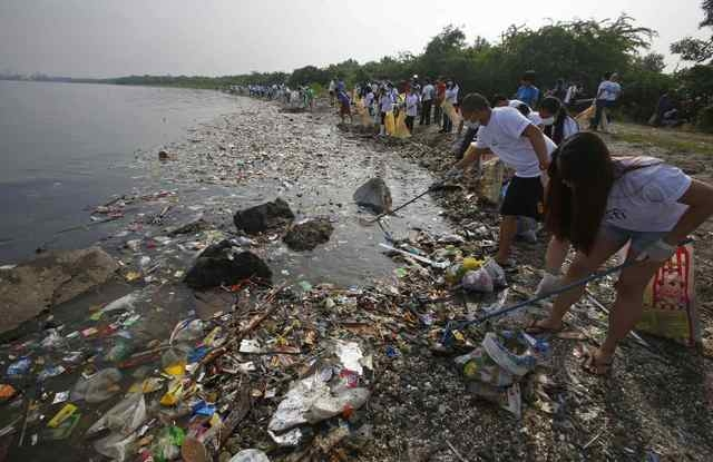 Volunteers collect garbage along the shore off Manila Bay, during an environmental project marking World Oceans Day in Paranaque, Metro Manila in this June 8, 2013 file photo. (Erik De Castro/Reuters)