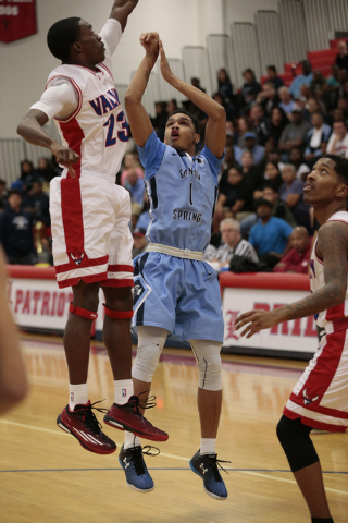 Canyon Springs High School Senior Jordan Davis (1) shoots a for a basket while Valley High School Senior Nick Brannon (23) attempts to block the shot during the first half of the NIAA Sunrise Regi ...