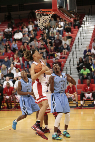 Valley High School Senior Taveon Jackson (4) grabs the rebound infront of Canyon Springs High School Senior D'Quan Crockett (21) during the first half of the NIAA Sunrise Region Boys  basketball c ...