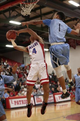 Canyon Springs High School Senior Jordan Davis (1) jumps up to block a shot by Valley High School Senior Taveon Jackson (4) during the first half of the NIAA Sunrise Region Boys  basketball champi ...