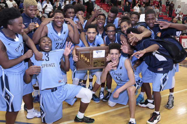 The Canyon Springs team poses with the trophy award after winning in triple overtime against the Valley Vikings with a score of 65 to 63 at the NIAA Sunrise Region Boys  basketball championship ga ...