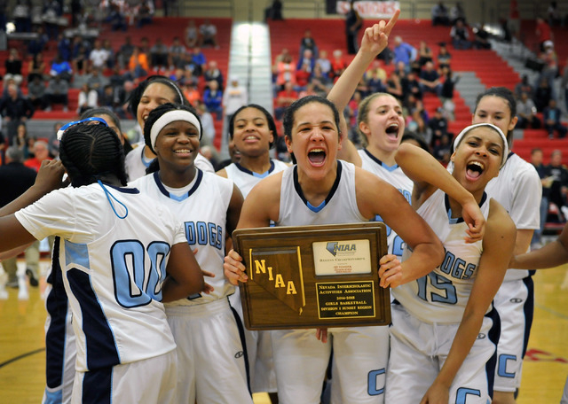 Centennial's Karina Brandon, center, holds the championship trophy after the Bulldogs defeated Bishop Gorman at the Sunset Region girls basketball championship game at Arbor View High School in La ...