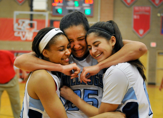 Centennial team members from left, Alex Dockery, Karina Brandon and Sarah Kruthaupt embrace after the Bulldogs defeated Bishop Gorman at the Sunset Region girls basketball championship game at Arb ...