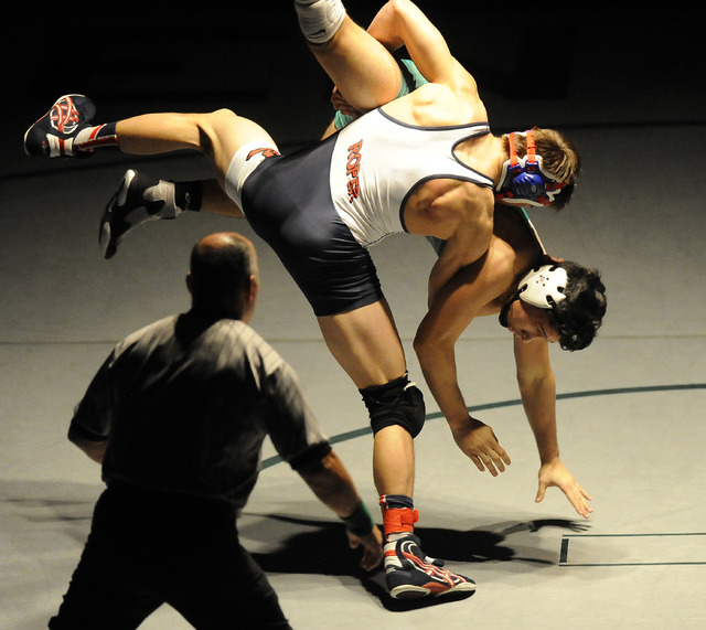 Storm Roper of Liberty, center, slams Giullian Nakamatsu of Green Valley, to the mat during the 152 pound final of Sunrise Region Wrestling tournament at Green Valley High School in Henderson, Sat ...