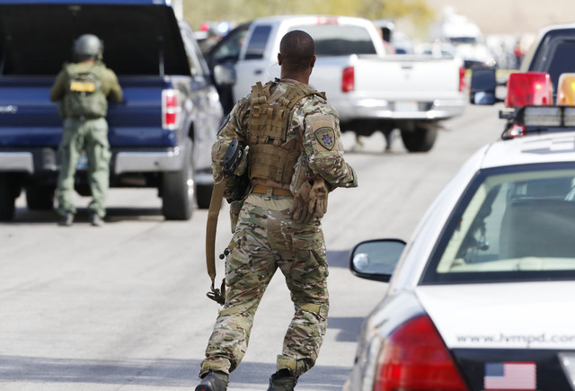 A SWAT team is seen in the 7900 block of Cherry River Drive Thursday, Feb. 19, 2015, near a house where an individual believed to be involved in the deadly road rage incident was arrested. (Bizuay ...