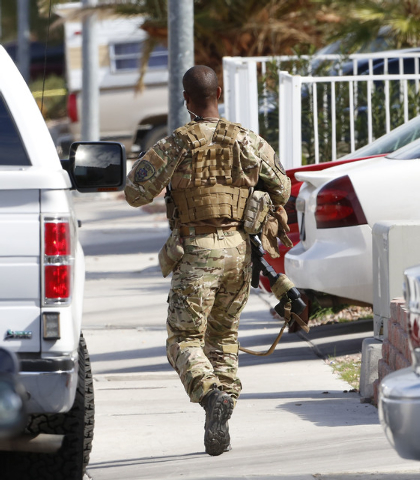 A SWAT officer is seen in the 7900 block of Cherry River Drive Thursday, Feb. 19, 2015, near a house where an individual believed to be involved in the deadly road rage incident was arrested. (Biz ...