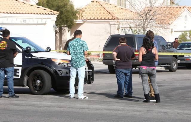 Residents on Cherry River Drive watch as metro police arrested an individual believed to be involved in the deadly Feb. 12 road rage incident, Thursday, Feb. 19, 2015. He was taken into custody at ...