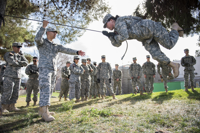 ROTC cadet Elijah Armstrong, 20, third from left, helps cadet Zoe Bogikes, 31, conduct the commando crawl during a rope-bridge leadership drill at the UNLV practice football field on the UNLV camp ...