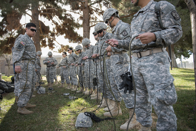 ROTC cadet James Querubin, 21, left, assists other cadets with tying an improvised climbing harness during a rope-bridge leadership drill at the UNLV practice football field on the UNLV campus in  ...