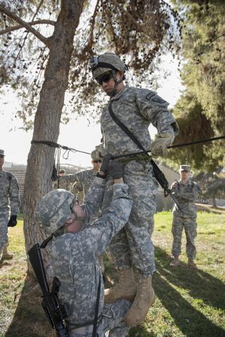 ROTC cadet Garrett Rhodes, 20, left, assists cadet James Querubin, 21, during a rope-bridge leadership drill at the UNLV practice football field on the UNLV campus in Las Vegas on Friday, Feb. 6,  ...