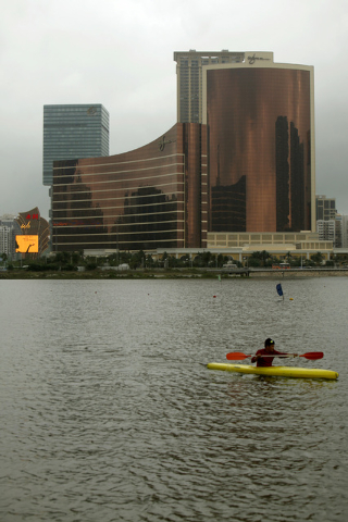 A man canoes in front of The Wynn Macau hotel (L) and Wynn Encore casino and hotel in Macau April 21, 2010. The $600 million Encore with 414 suites and villas, opened on Wednesday.  REUTERS/Tyrone ...