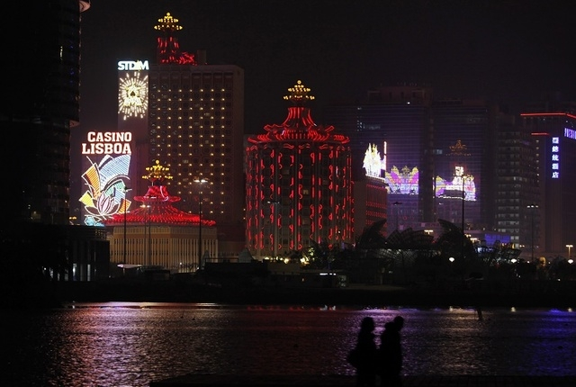 A couple walks on a waterfront in front of Casino Lisboa, owned by Sociedade de Turismo e Diversoes de Macau S.A.R.L. (STDM), in Macau on the evening of April 4, 2011. (Bobby Yip/Reuters)