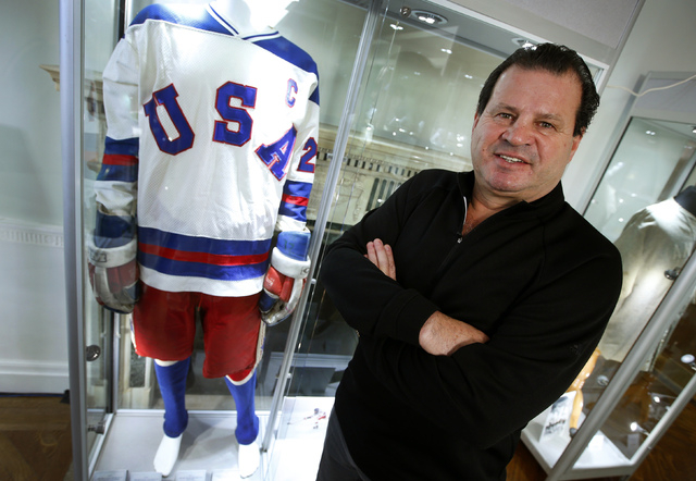Mike Eruzione, captain of the 1980 gold medal winning U.S. Olympic ice hockey team poses next to the jersey and uniform he wore when the U.S. defeated the Soviet Union in what is known as the &quo ...