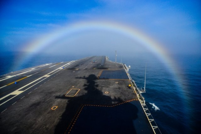 Navy photographer Ignacio Perez captured a shot of the USS John C. Stennis 1,100-foot-long warship as it was cruising in the Pacific Ocean steaming through a rainbow on Feb. 3, 2015.  (CNN/SPC Ign ...