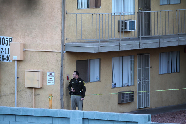 Las Vegas police officers investigate the scene of a shooting at the Siegel Suites apartments near the intersection of E. Twain Avenue and Swenson Street in Las Vegas Tuesday, Feb. 24, 2015. (Erik ...