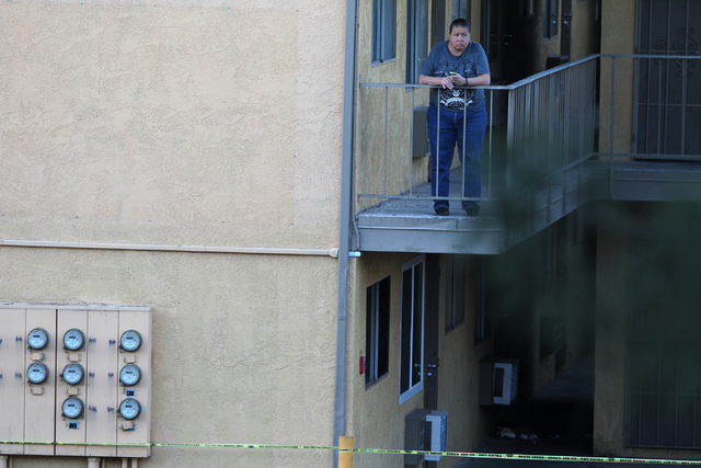 An unidentified woman stands on a balcony at the Siegel Suites apartments where Las Vegas police officers investigate a shooting near the intersection of E. Twain Avenue and Swenson Street in Las  ...
