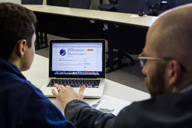TMS Microbank faculty adviser Adam Betzelberger, right, analyzes possible investments with sophomore Michael Blau, who will be the group's president beginning in is junior year, at The Meadows Sch ...