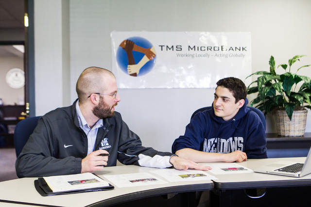TMS Microbank faculty adviser Adam Betzelberger, left, analyzes possible investments with sophomore Michael Blau, who will be the group's president beginning in is junior year, at The Meadows Scho ...
