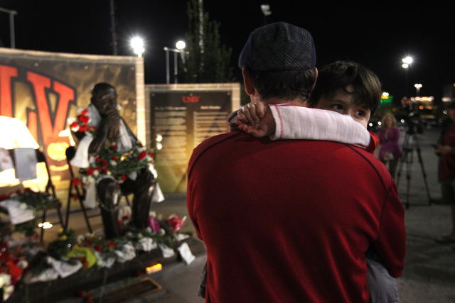 Jerry Tarkanian's son Danny Tarkanian holds his son, Jerry, during a vigil for the former UNLV basketball coach  who passed away Wednesday, Feb. 11, 2015. (Sam Morris/Las Vegas Review-Journal)