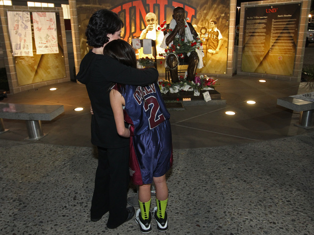Daughter-in-law Amy Tarkanian hugs her daughter Lois as they visit a statue of Jerry Tarkanian during a vigil for the former UNLV basketball coach  who passed away Wednesday, Feb. 11, 2015. (Sam M ...
