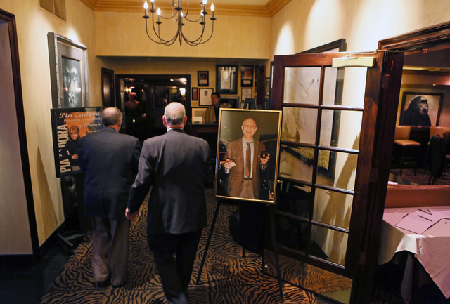 Patrons walk past a photo of Jerry Tarkanian at Piero's Italian Cuisine Monday, Feb. 16, 2015, in Las Vegas. Restaurant owner Freddie Glusman welcomed Tarkanian friends and fans to a recept ...