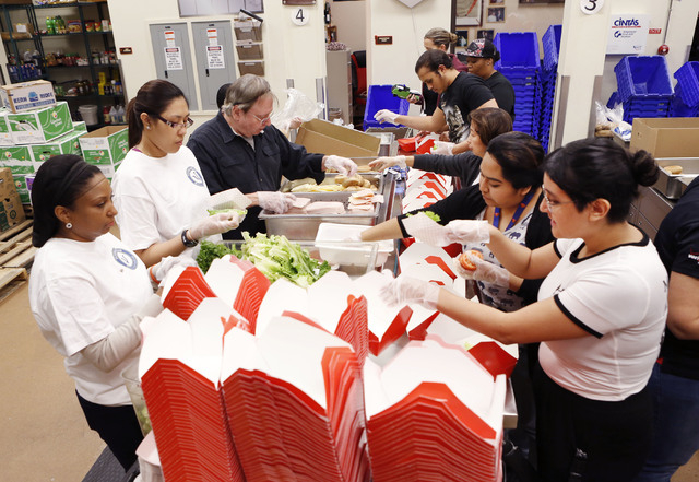Volunteers at Three Square Food Bank prepare lunch boxes Friday, Feb. 20, 2015, at 4190 North Pecos Road. Three Square Bank received a new contribution of $10 million from the Ralph and Betty Enge ...