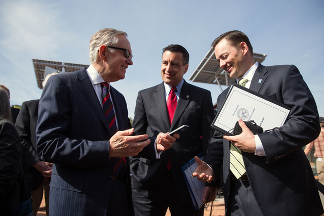 """U.S. Sen. Harry Reid, D-Nev., left, Gov. Brian Sandoval, center, and Paul Thomsen, Director of the Nevada Office of Energy, talk in front of solar trees at the """"Welcome to Fabulous Las Vegas""""  ..."""