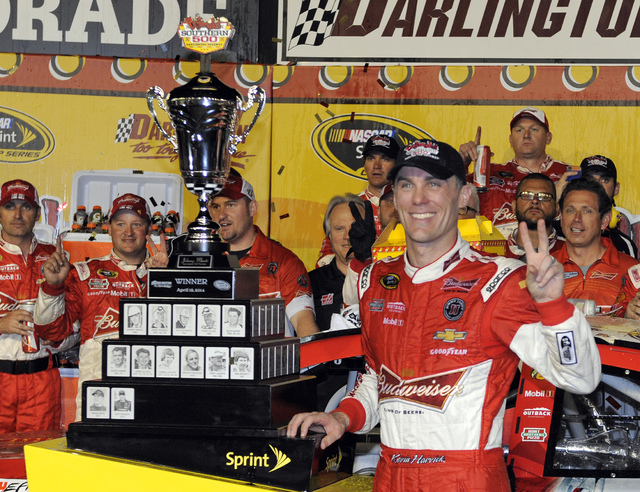 Kevin Harvick poses with the trophy in Victory Lane after winning the NASCAR Sprint Cup series auto race at Darlington Raceway in Darlington, S.C., Saturday, April 12, 2014. (AP Photo/Mike McCarn)