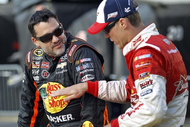 In this May 22, 2014, file photo, Tony Stewart, left, talks with Kevin Harvick before qualifying for a NASCAR Sprint Cup series auto race at Charlotte Motor Speedway in Concord, N.C. Stewart is sk ...