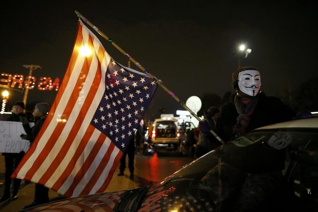 A protester wearing a Guy Fawkes mask holds the U.S. flag outside the Ferguson Police Department in Ferguson, Missouri, November 24, 2014. (REUTERS/Jim Young )