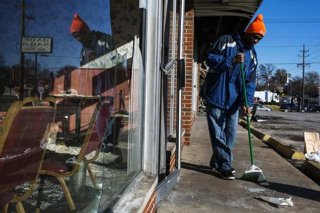 Volunteer Johnathan Johnson helps to clean a sidewalk outside of a restaurant that had been burned and damaged following a night of rioting in Ferguson, Missouri November 25, 2014. (REUTERS/Lucas  ...
